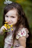 Långhårig flicka med gula blommor Royaltyfria Bilder