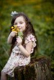 Långhårig flicka med gula blommor Arkivbild