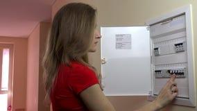 Långhårig kvinna som är roterande på ljus-strömbrytaren på maktkontrollbordet hemma stock video