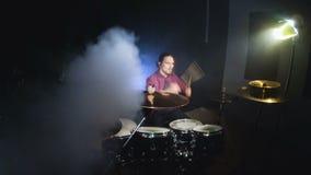 Långhåriga handelsresande spelar valssatsen i ett mörkt rum på en svart bakgrund white för rock för bakgrundsmanmusiker Statiskt  stock video
