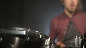Långhåriga handelsresande spelar valssatsen i ett mörkt rum på en svart bakgrund white för rock för bakgrundsmanmusiker Statiskt  arkivfilmer