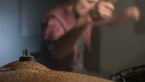 Långhåriga handelsresande spelar valssatsen i ett mörkt rum på en svart bakgrund white för rock för bakgrundsmanmusiker Statiskt  lager videofilmer