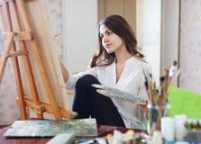 Långhåriga kvinnliga konstnärmålarfärger med olje- målarfärger royaltyfri fotografi