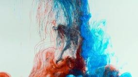 Långsam droppe av röd och blå målarfärg i vatten som följs, genom att upplösa och att blanda
