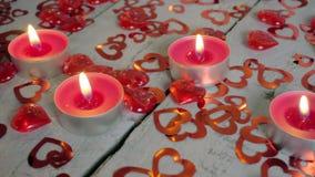 Långsam närbildglidbana av tända upp stearinljus på den wood tabellen med röda hjärtor omkring red steg