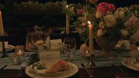 Långsam panna av ferietabellen med portionen, giffel, stearinljus, makron, blommor