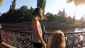 långsam rörelse Den gulliga ungesyskongruppen som går vid floden i staden, parkerar stock video