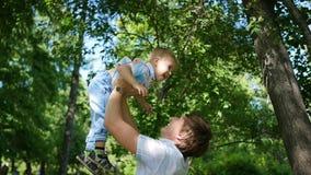 långsam rörelse en ung fader som kastar hans skratta, behandla som ett barn upp i luften utomhus- rekreation för lunch arkivfilmer