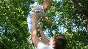 långsam rörelse en ung fader som kastar hans skratta, behandla som ett barn upp i luften utomhus- rekreation för lunch stock video