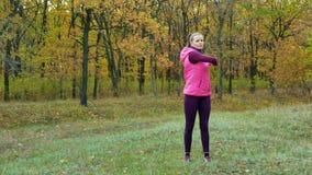 långsam rörelse Härlig konditionsportflicka i sportsweardrinkvatten eller isotonic drink från en sportvattenflaska i hösten stock video