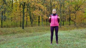 långsam rörelse Härlig konditionsportflicka i sportsweardrinkvatten eller isotonic drink från en sportvattenflaska i hösten arkivfilmer
