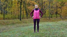långsam rörelse Härlig konditionsportflicka i sportsweardrinkvatten eller isotonic drink från en sportvattenflaska i hösten lager videofilmer