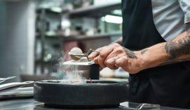 långsam rörelse Kantjusterad bild av restaurangkockhänder med flera tatueringar som tillfogar en krydda till ny lagad mat pasta C fotografering för bildbyråer