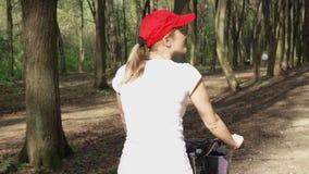 långsam rörelse Kvinnaridningcykel Den kvinnliga tonåringen som cyklar att cykla i soligt, parkerar Aktivt sportbegrepp stock video