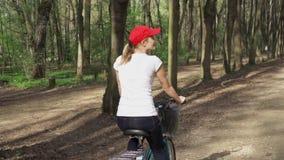 långsam rörelse Kvinnaridningcykel Den kvinnliga tonåringen som cyklar att cykla i soligt, parkerar Aktivt sportbegrepp lager videofilmer