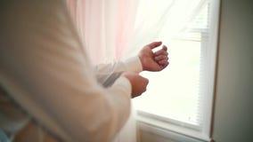 långsam rörelse Mannen för brudgumjraffären bär upp det vita skjortaslutet lager videofilmer