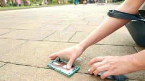LÅNGSAM RÖRELSE: Smartphonen faller på asfalten på gatan och delar in i delar 4K stock video