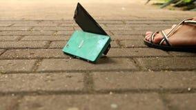 LÅNGSAM RÖRELSE: Smartphonen faller på asfalten på gatan och delar in i delar 4K arkivfilmer