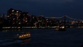Långsam slutare av East River, den 59th gatabron, fartyget och stadsljus Arkivbild