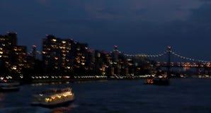 Långsam slutare av East River, den 59th gatabron, fartyget och stadsljus Royaltyfri Foto