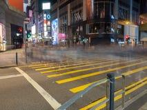 Långsam slutare med gångarekorsningen gatan i drottnings väg centrala Hong Kong royaltyfri bild