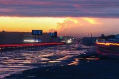 Långsam slutare på aftontrafik i regnspår Arkivfoton