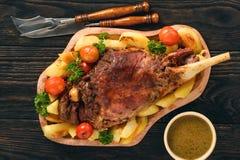 Långsamt bakat lammben med potatisar och sås royaltyfri bild
