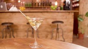 Långsamt glidande skott av ett exponeringsglas av martini i en tom restaurang lager videofilmer