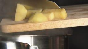 LÅNGSAMT: Kocken kastar en skivad potatis (nära övre) stock video