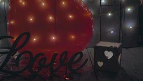 Långsamt närbildglidbanaskott av förälskelsetecknet med röda hjärtor, ljus och röd baloon på bakgrund red steg arkivfilmer