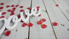 Långsamt närbildglidbanaskott av förälskelsetecknet med röda hjärtor omkring red steg