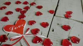 Långsamt närbildglidbanaskott av röd hjärta på pinnen med förälskelsetext på den, med röda hjärtor omkring red steg lager videofilmer