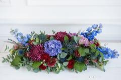 Långsträckt blom- ordning i tappningmetallvas Table inställningen blå och röd färg Ursnygg bukett av olikt royaltyfri foto