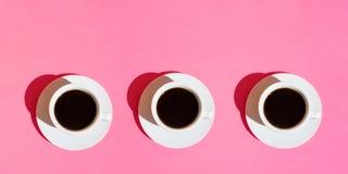 Långt baner för kaféstänger Vita koppar kaffe med tefatet på bakgrund för färg för neonfuchsiarosa färger Top beskådar royaltyfria bilder