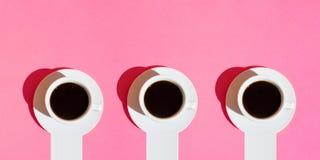 Långt baner för kaféstångaffär Vita koppar kaffe med bakgrund för rosa färger för fuchsia för neon för tefatDigital beståndsdelar arkivfoto