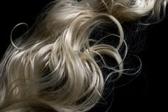Långt blont hår på svart bakgrund Arkivfoto