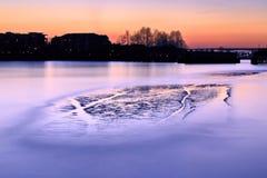 Långt exponeringsfoto av en flod med en holme på solnedgången Arkivfoton