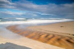 Långt exponeringsfoto av en flod som igenom bryter in i havet arkivfoton