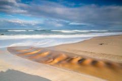 Långt exponeringsfoto av en flod som igenom bryter in i havet royaltyfria foton