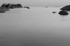 Långt exponeringsfoto av stranden i aftonen som är svartvitt Fotografering för Bildbyråer