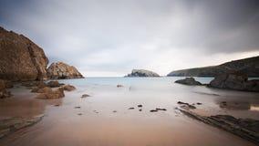 Långt exponeringsfoto på en strand full av rocks Arkivfoto
