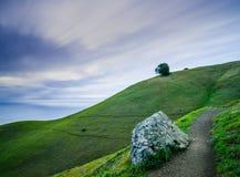 Långt exponeringsfotografi med rörande moln, en bana som leder av, gröna kullar och det släta havet royaltyfri foto
