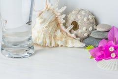 Långt exponeringsglas av vatten på det vita träskrivbordet Arkivbilder