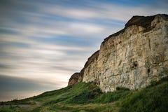 Långt exponeringslandskap av himmel för rörelsesuddighet över vibrerande klippor Arkivfoton