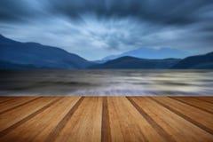 Långt exponeringslandskap av stormig himmel och berg över sjö w Fotografering för Bildbyråer