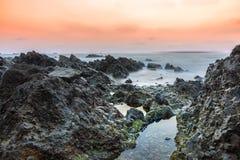 Långt exponeringslandskap för lågt ljus av solnedgången över den steniga stranden Royaltyfria Bilder