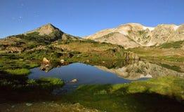 Långt exponeringsnattskott av medicinpilbågebergen av Wyoming, den alpina sjön och stjärnor Arkivfoto