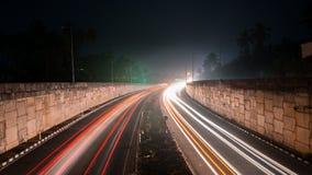 Långt exponeringsskott av en upptagen motorväg på natten arkivfoton