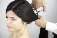 Långt hår för läskigt ögonblick som klipps av frisören arkivfoton