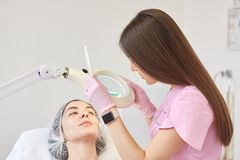 Långt haired kosmetologanseende nära hennes klient och att trycka på förstoringsglaset och att hålla ögonen på till och med det,  arkivfoton